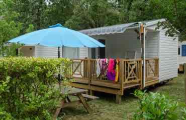 Mobil-Home - locations mobil home en version 2 ou 3 chambres. Possibilité de climatisation. Terrasse extérieure couverte avec salon de jardin.