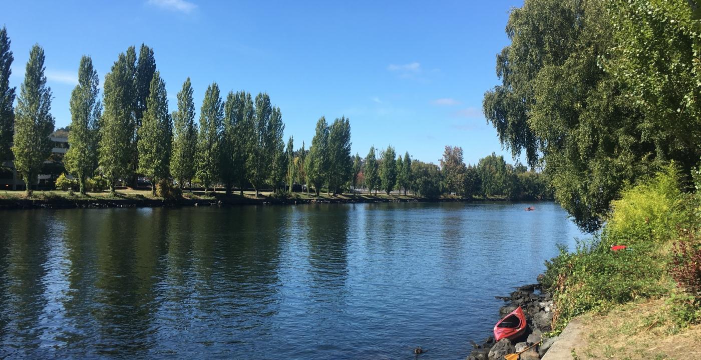 Large rivière et kayak amaré sur la rive